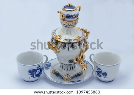 A set of porcelain tableware tea from a samovar with a teapot and two cups and saucers, made in Gzhel style. Closeup. Isolated on white. #1097455883