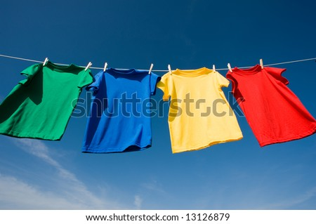 a set of primary colored T-shirts hanging on a clothesline on a beautiful, sunny day, add text or graphic to shirts or copy space #13126879