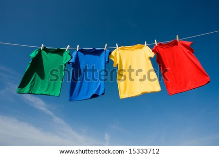 a set of primary colored T-shirts hanging on a clothesline on a beautiful, sunny day, add text or graphic to shirts or copy space #15333712