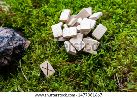A set of Scandinavian runes made on wooden planks lies on a natural moss, next to the Gebo rune, attracting the gifts of God. Fortune telling tool, concept for predicting the future.