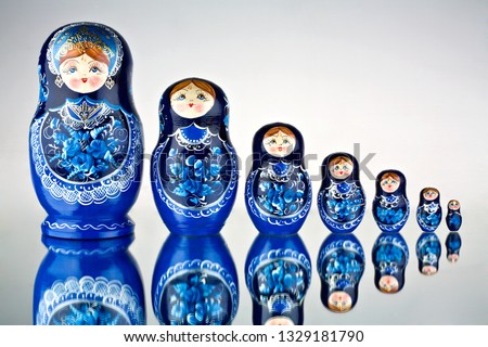 A set of seven blue painted Russian nesting dolls on mirror surface. Creative concept photo of set of seven blue painted national toys Russian nesting dolls on mirror surface.