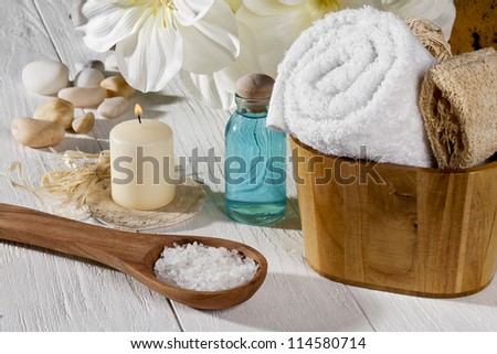 A set of spa products with spa salt on a spoon, towel, oil and a lighted candle on a wooden table