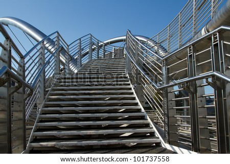 A set of stainless steel steps leads to a bridge with safety hand railings with a blue sky in the background.