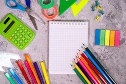 A set of stationery. Calculator, notepad, colored pencils, rulers, felt-tip pens, scissors  and colorful stickers on a gray background. Space for text, background. Flat lay, top view