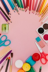 A set of stationery: watercolor, pencils, crayons, gouache, pen, scissors, sharpener, eraser isolated on colorful pink background. Minimal concept art. Education, creativity and school supplies.