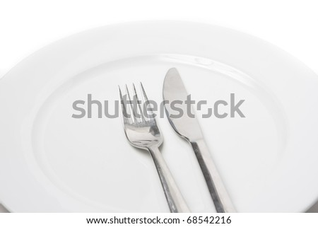 A set of steel fork and knife on a white plate