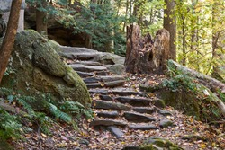 A set of stone stairs on a trail in a forest in Cuyahoga Valley Naitonal Park. the trail leads through the woods and beside some rock ledges.
