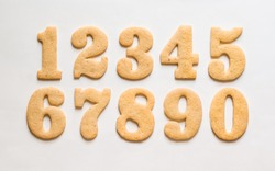 A set of sugar cookie numerals / gingerbread cuted in the form of numbers one, two, three, four, five, six, seven, eight, nine, zero on a white background.