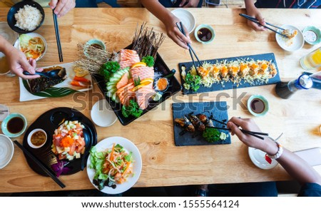 A set of sushi on a wooden table in a Japanese restaurant.Fresh salmon sliced for sushi menu.Party of friends or family eating sushi using bamboo sticks.