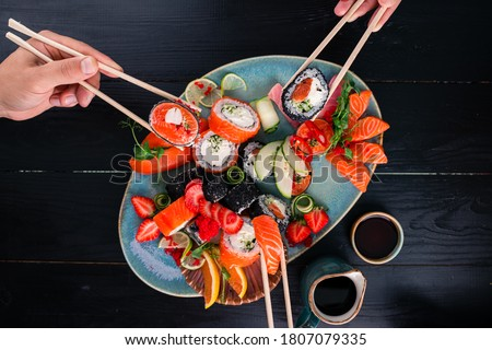 A set of sushi on a wooden table in a Japanese restaurant. sushi and sashimi on sticks, friends eat rolls in a Japanese restaurant top view Party of friends or family eating sushi