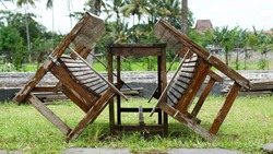 A set of the old wooden bench and table, close-up shots outdoor on the grass fields with blurred background.