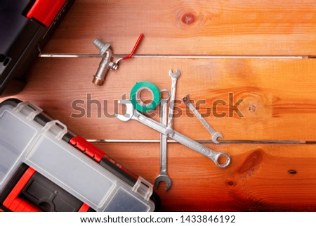 A set of tools and two tool boxes are laying on a wooden surface