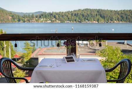 A set table with a reserved sign and an ocean view overlooking Gibsons harbor