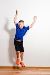 A seven-year-old short-haired boy jumps in sneakers against a white background. Children and sport
