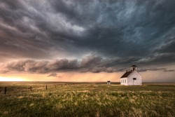 A severe thunderstorm approaches an old abandoned church in the countryside during the late afternoon in Colorado.