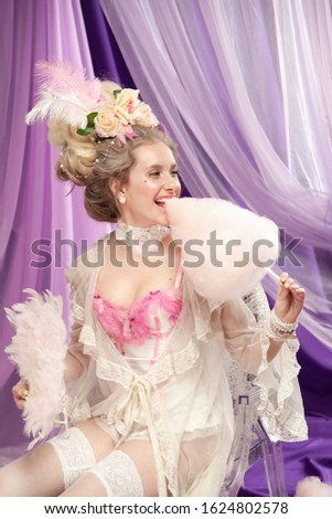 A sexy girl, in a romantic negligee, stylized as the Marie Antoinette style, with a high hairdo decorated with flowers and feathers, in a boudoir, laughs and eats cotton candy.