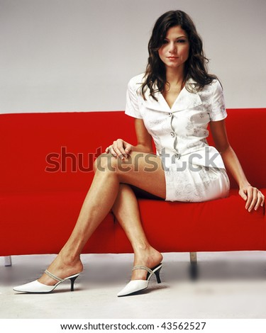 A sexy model sitting on a bright red couch in the studio.