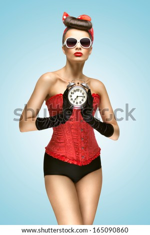 A sexy photo of pin-up girl in vintage corset, panties and gloves holding old clock.