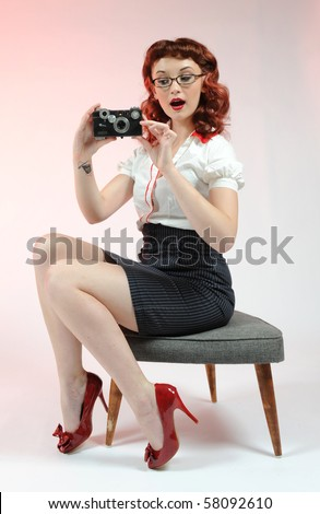 A sexy pin up librarian with a vintage camera. - stock photo
