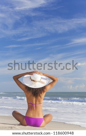 A sexy young brunette woman or girl wearing a bikini and sun hat sitting on a deserted tropical beach with a blue sky