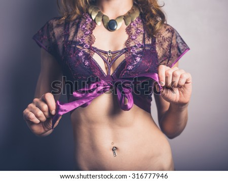 A sexy young woman is wearing exotic lingerie and a necklace