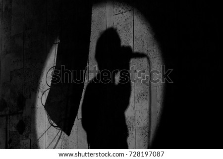 A shade silhouette of a band singer singing into his microsophone in a round spotlight #728197087