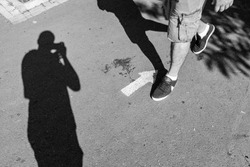 a shadow of a street photographer sealing the legs of a man walking against a painted arrow. street black and white photography.