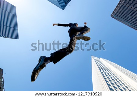 A  shadow of businessman jumping with the blue sky and skyscrapers background . Energetic · Power · Success · Challenge Image #1217910520