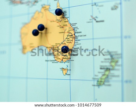 A shallow depth of focus picture with a blurred background of a map of Australia with pushpins marking locations visited. Focus centered on Sydney and other cities on the eastern coast.