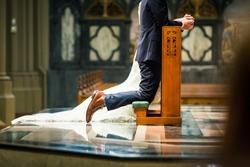 A shallow focus shot of a bride and groom kneeling on a prayer kneeler inside the church