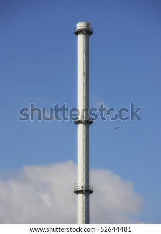 A sharp photo of an isolated tall factory chimney. Symbolic content.