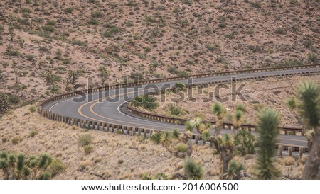 A sharp turn through the desert canyons on E Diamond Bar Road. Meadview, Mohave County, AZ. The single lane (in each direction) street connects to the West Rim of Grand Canyon. Joshua trees in bokeh. Foto stock ©
