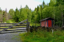 A sheep farm with a shed in a Scandinavian (Norwegian) style, hidden in the woods behind Lillehammer, in cold but sunny Norway.