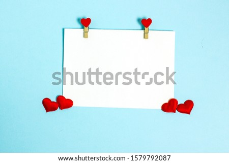 A sheet for congratulations on Valentine's Day. Valentine's Day flat lay copy space. Top view on a blue background a sheet of white paper for a text of congratulation and red hearts.