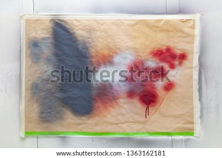 A sheet of paper attached to the wall with scotch tape stains from splashing paint to test color before painting #1363162181