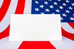 A sheet of paper on the background of the American flag. Mockup with the American flag. Flag of the United States of America and white space for text . Patriotic American frame.