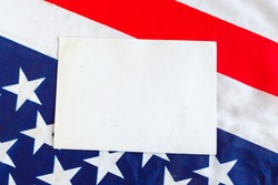 A sheet of paper on the background of the American flag. Mockup with the American flag. Flag of the United States of America and white space for text