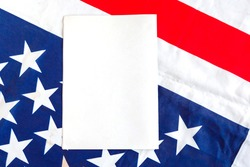 A sheet of paper on the background of the American flag. Mockup with the American flag. Flag of the United States of America and white space for text.