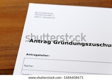 A sheet of paper with the german words 'Antrag Gründungszuschuss' - Translation in englisch: Application for a start-up grant. Stockfoto ©