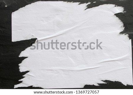 A sheet of white paper glued on a black wall.