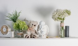 a shelf with a decorative clock and a teddy bear. Home interior of the room