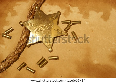 A sheriff badge and gun shells on some antique paper.