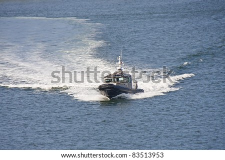 A sheriff's cruiser cutting through the water in a blue bay