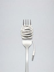 A shining fork with noodle made of cable with music jack plug in metal background.