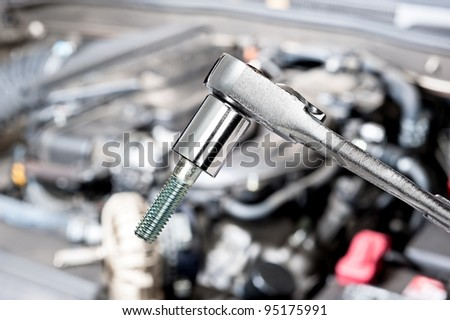 A shiny chrome socket wrench in front of a car engine before for servicing and repair