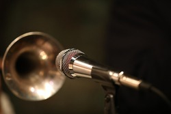 A shiny microphone in front of the blurry bell of a nightclub player's brass trumpet instrument.Art photography.Musical background.Close-up