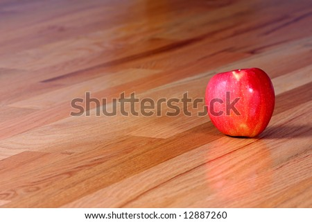 A shiny red apple on a hardwood floor.