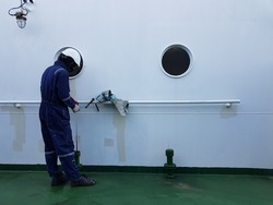 a ship crew is taking sounding of a ballast tank for draft survey calculation on aboard a cargo ship or bulk carrier.
