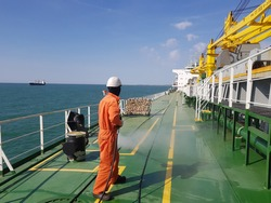 a ship crew is using high pressure washer to wash on ship main deck.