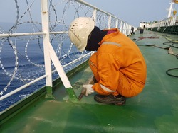 a ship crew is using jet chisel to remove rust maindeck for during maintenance